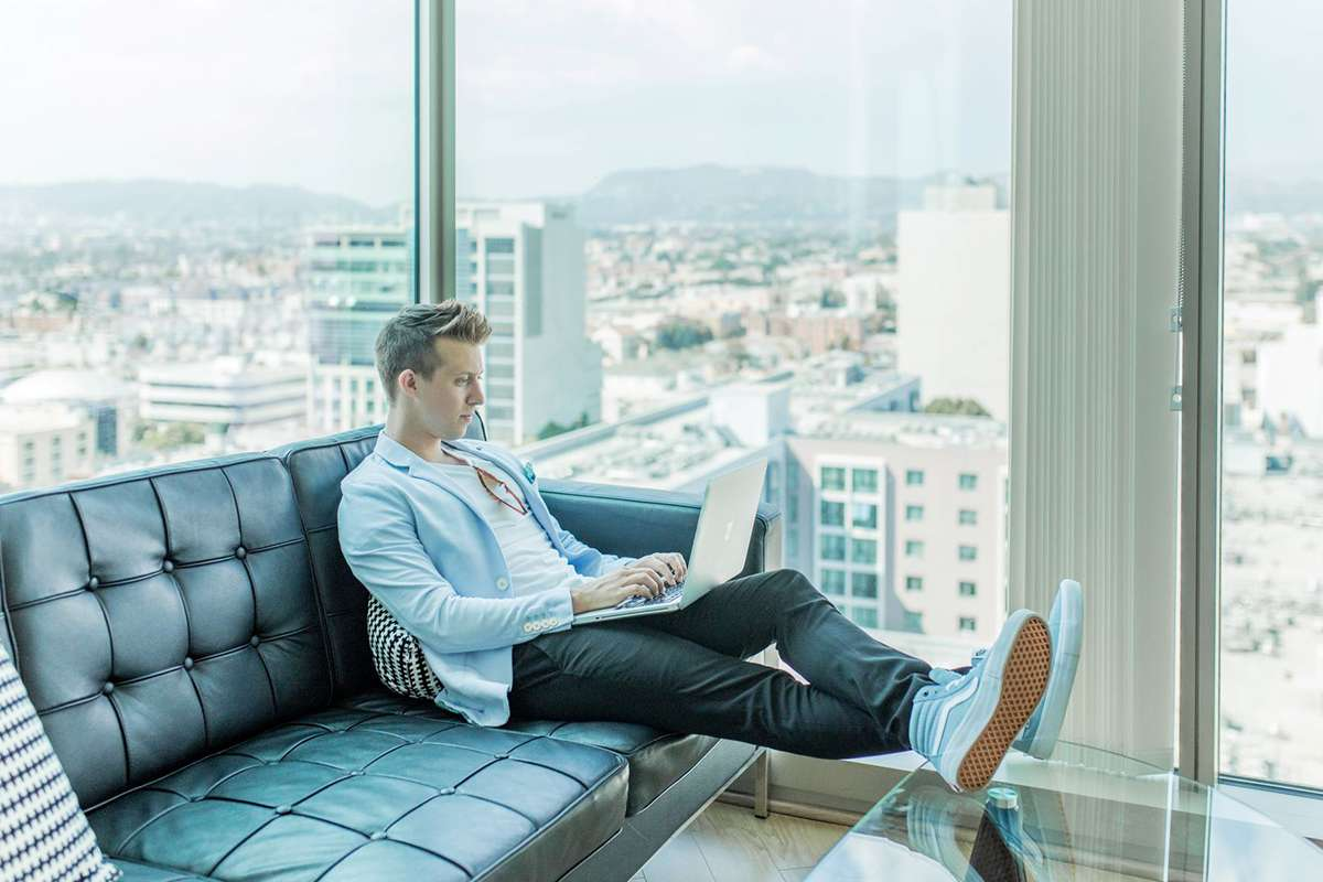 Man in high rise apartment sitting on sofa with laptop