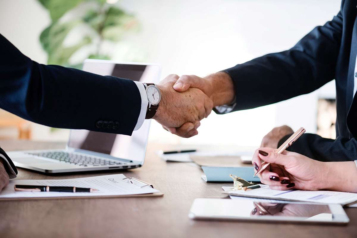 Two people shaking hands making a deal